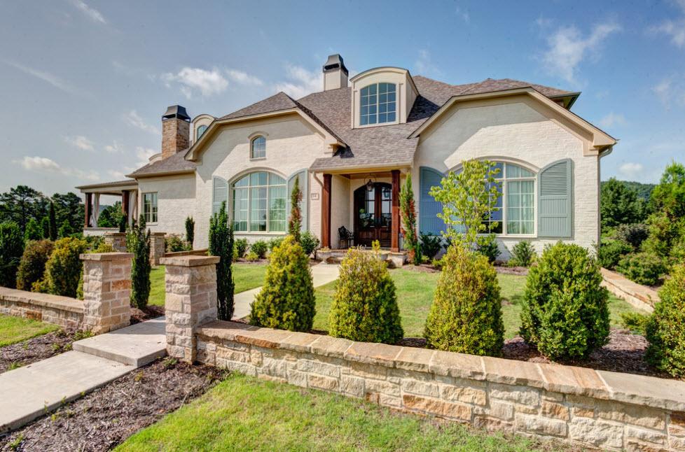 большой дом бежевого цвета с ломаной крышей