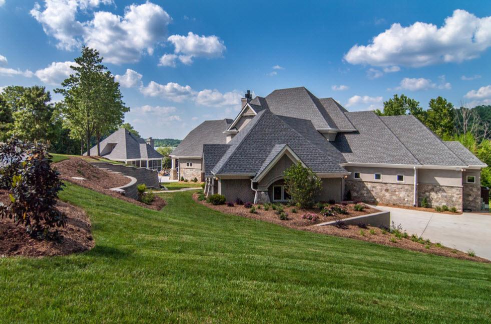 большой серый дом с вальмовой крышей сложной конструкции