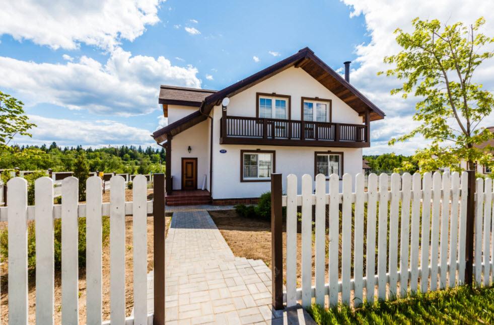 белый дом с классической отделкой и крышей в коричневом цвете