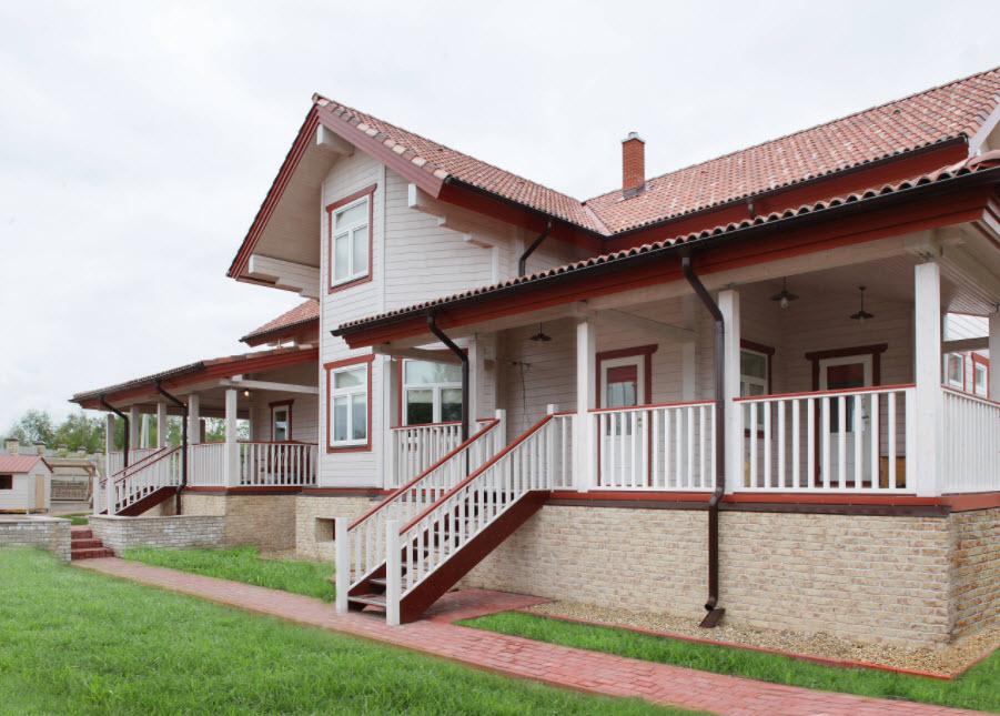 белый дом с красной отделкой и крышей