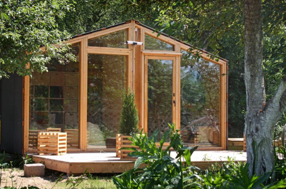 дом со стеклянными стенами и двухскатной крышей