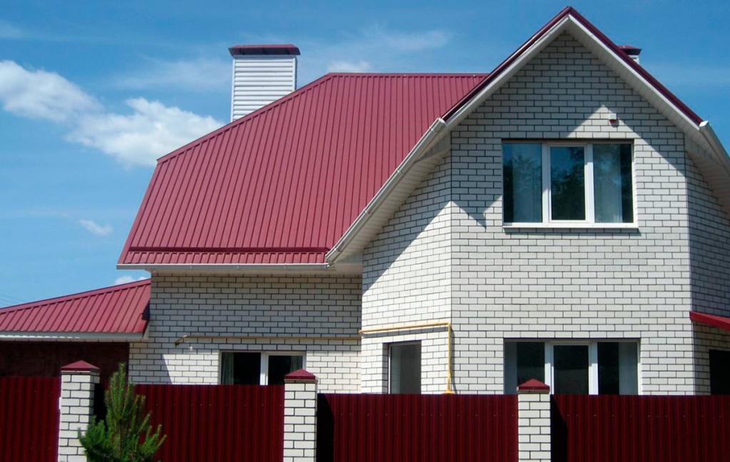 дом из белого кирпича с ломаной крышей из профнастила